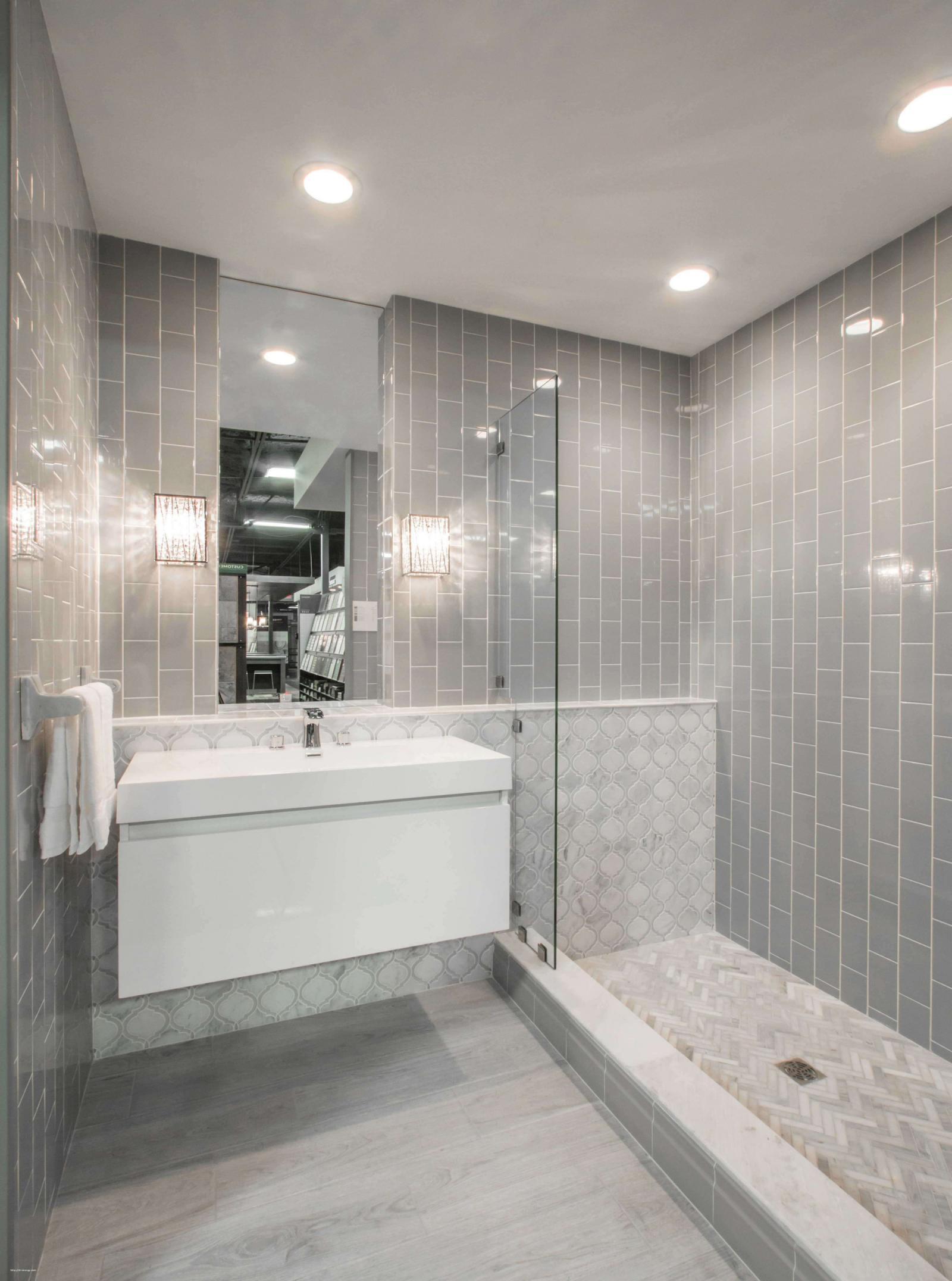 Phòng tắm với bồn rửa tay màu trắng lớn, vách kính, tường ốp gạch xám.